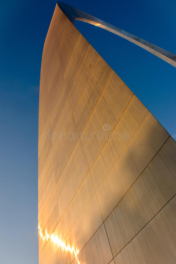 The giant Gateway Arch glitters. The metal surface glitters in the sun set of the elegant, giant and majestic Gateway Arch in St Louis, Missouri. An stock photos