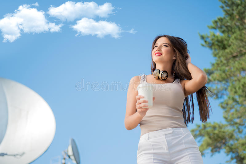 Giant and global. Happy young woman wearing vintage music headphones around her neck, holding takeaway coffee and posing against background of parabolic stock photography