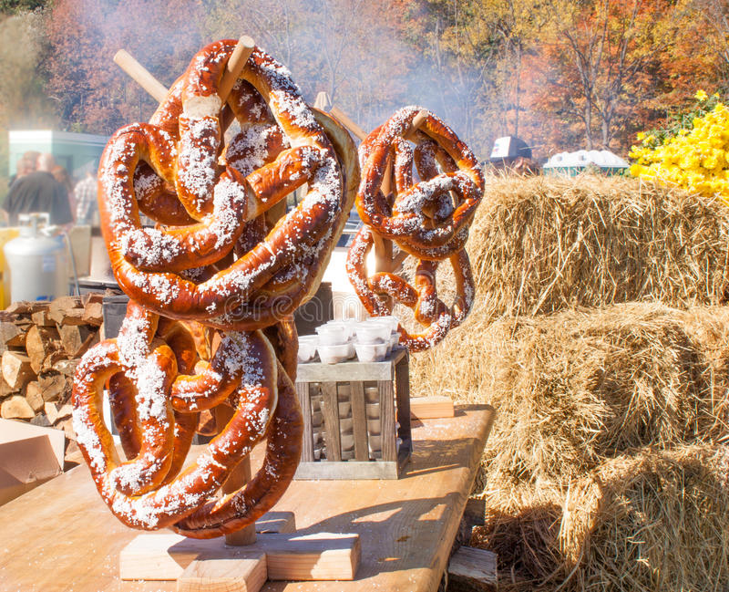 Giant homemade pretzels on display at Harvest Festival in Vernon New Jersey. Giant salted homemade pretzels for sale with bushels of hay and fall foliage in stock photography