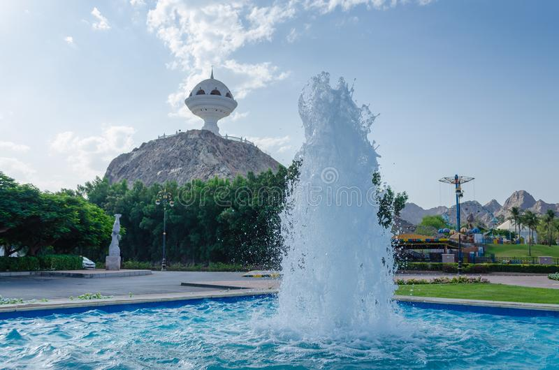 Water fountain in a park in Muscat, Oman. Water fountain in a park with the incense burner monument in the background at Riyam Park, Muttrah, Muscat, Oman stock photos