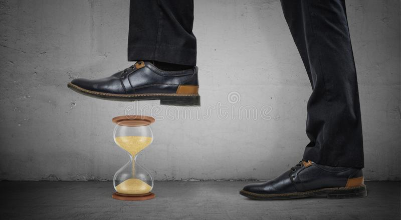 Giant male legs in shiny boots stand on concrete background and step on a small hourglass. Work in deadline. Crash time wasters. Results against timetable stock photos