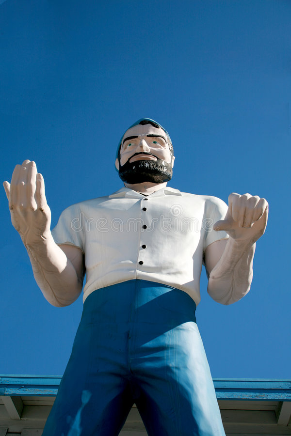 Giant man stature. A giant man stature used for advertising sits infront of a building outside royalty free stock photo