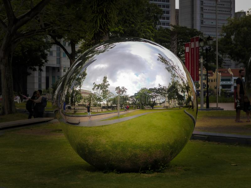 Giant Mirror Ball Sphere in Singapore City Centre. A Giant Silver Mirror Ball Sphere in a park in Singapore getting a fish-eye look distorted reflection of stock photography