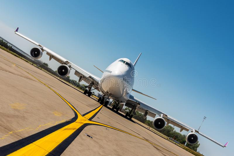 Giant modern civil passenger airliner at airport. Front view of the aircraft. Unique perspective. Summer travel concept royalty free stock photography