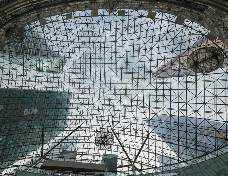 Giant modern glass buildings are visible through the glass ceiling of the building located in the center. Skyscrapers reach the sk. Y in the urban landscape stock image