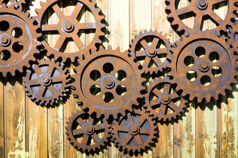 GIANT OLD AND RUSTY COGWHEELS ON THE WALL. GIANT OLD AND RUSTY COGWHEELS ON THE WOODEN WALL royalty free stock photography