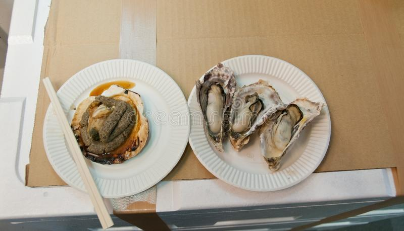 Giant oysters and grilled scallop at Tsukuji Tokyo fish market. Giant oysters and grilled scallop at Tsukuji famous Tokyo fish market stock images