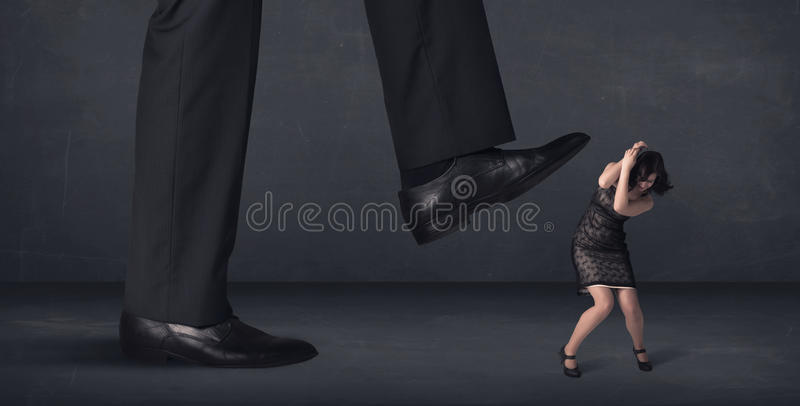 Giant person stepping on a little businesswoman concept. On background royalty free stock images