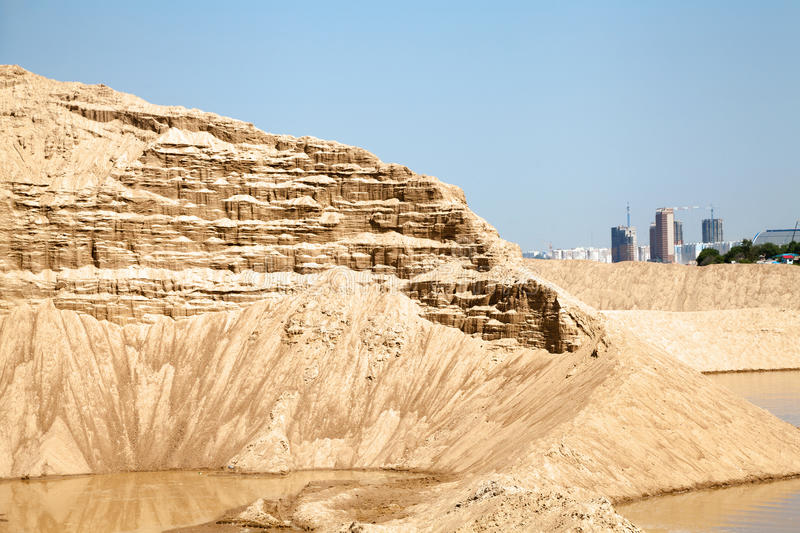 Giant pile of sand against the blue sky. Sand extraction mine. Beautiful industrial sunny landscape stock photos