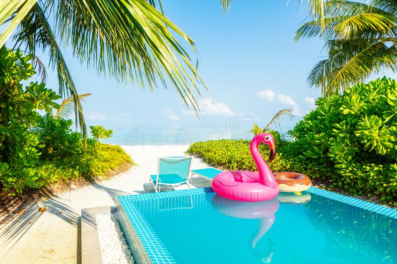 Giant Pink inflatable swan by blue pool water at laxery tropical villa. Summer vacation holiday concept. Giant Pink inflatable flamingo by blue pool water at royalty free stock photo