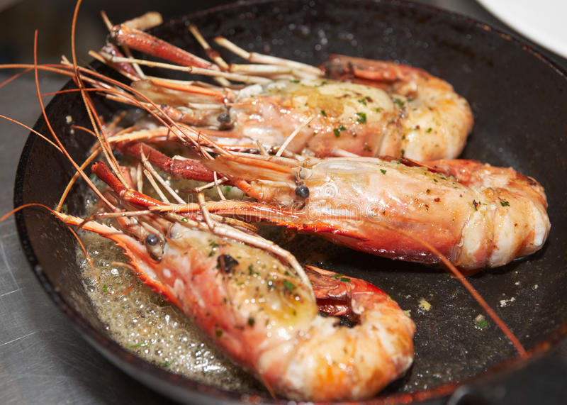 Giant prawns on hot pan. Stir fried in butter royalty free stock images