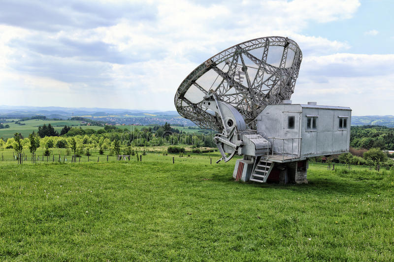 Giant radio telescope with silver control booth. On lawn and cloudy sky royalty free stock images
