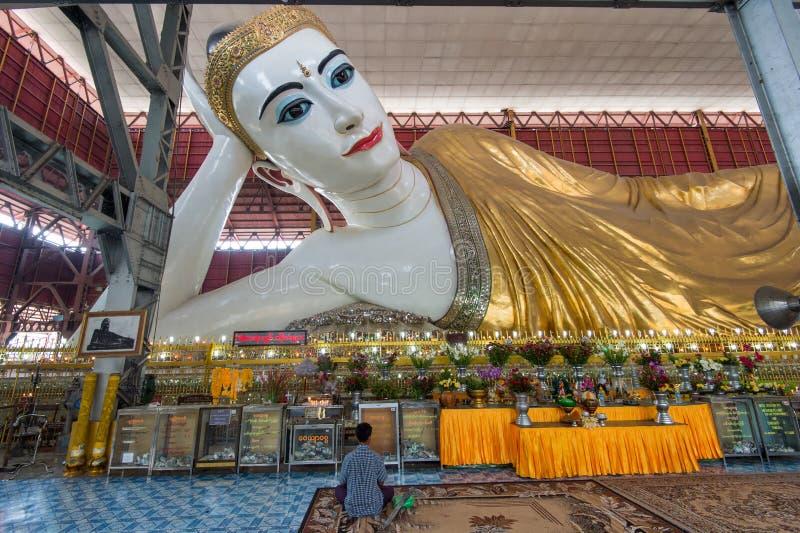 Giant reclining Buddha in Yangon. Yangon, Myanmar - February 10, 2014: Burmese man worships in front of reclining Buddha at Chauk Hhat Gyi Pagoda. The Buddha is royalty free stock photo