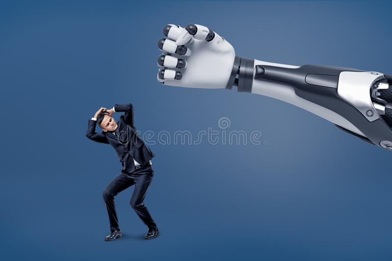 A giant robotic hand is ready to hit a tiny scared businessman with a fist. royalty free stock image