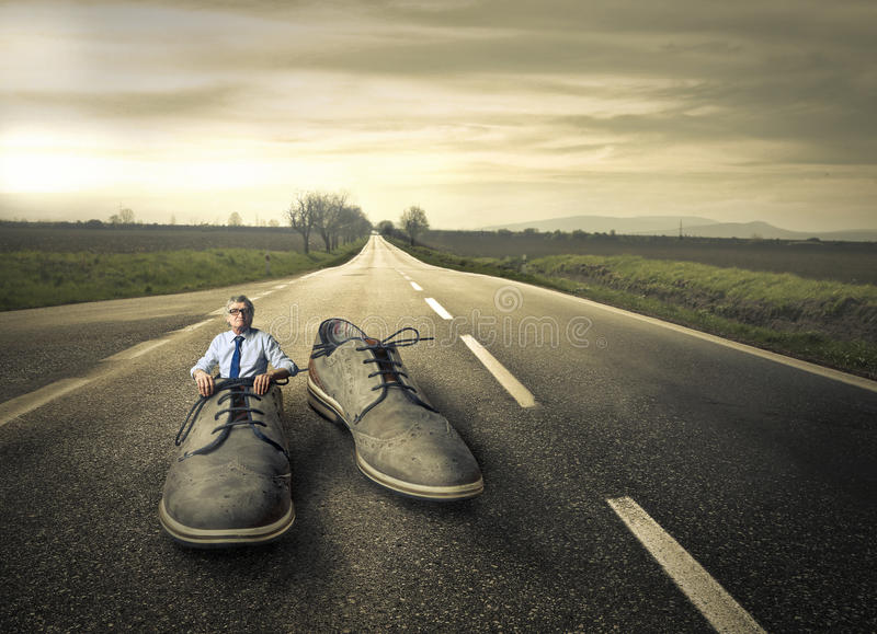 Giant shoes. Man stuck in giant shoes in the middle of the road royalty free stock images