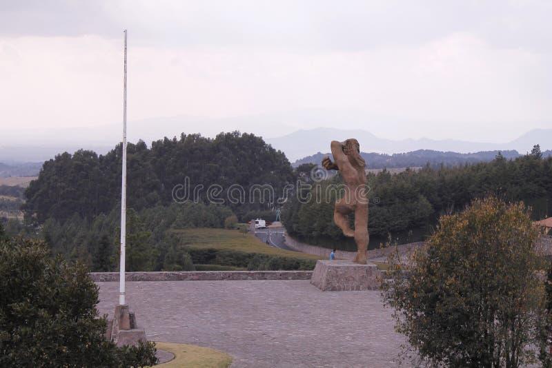 Giant Statue and a flag`s stick at Centro Ceremonial Otomi in Estado de Mexico. The giant statue at the entrance in Centro Ceremonial Otomi, located near Toluca stock image