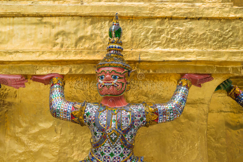 The giant statue supporting golden pagoda in the temple of the Emerald Buddha (Wat Phra Kaew) , Bangkok, Thailand royalty free stock photos