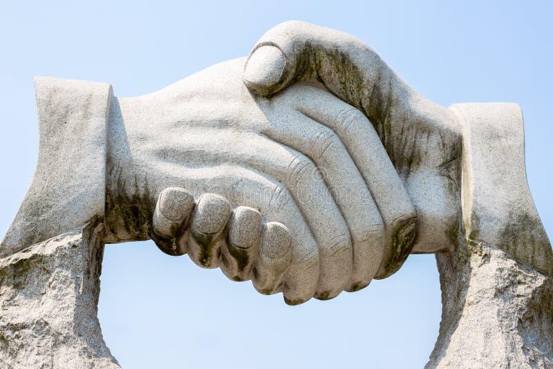 Giant stone handshake stock photography