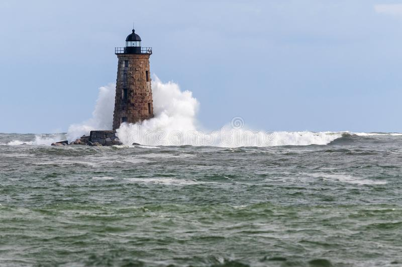 Giant Wave Surrounds Stone Lighthouse in Maine stock photo