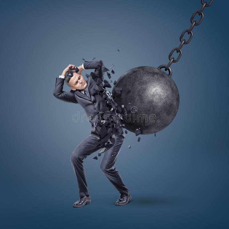 A giant wrecking ball hits a scared businessman and breaks him in pieces. royalty free stock photography
