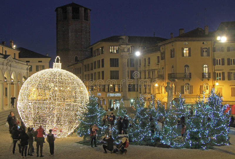 The giant xmas ball outdoor in Udine, Italy. Udine, Italy - November 20, 2015: people are walking nearly the giant xmas ball outdoor in Udine, Italy stock photo