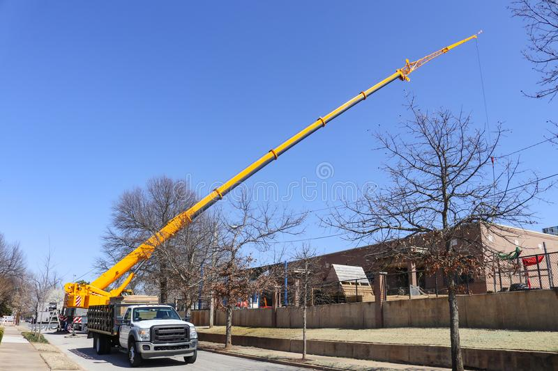 Giant yellow crane set up on blocked urban street stretching up above building lowering something down into it stock images