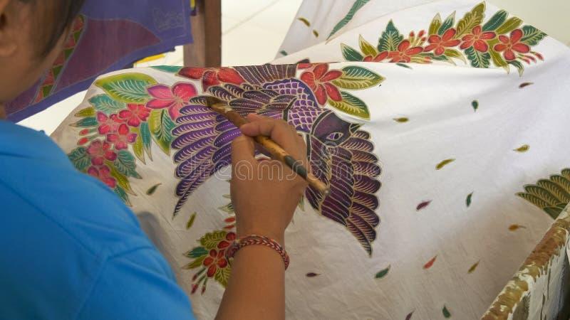 GIANYAR, INDONÉSIA - 19 DE JUNHO DE 2017: fechamento de um artista pintando um pássaro em tecido batik em bali fotos de stock royalty free