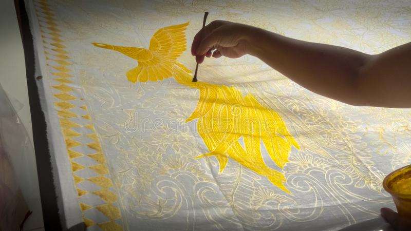 GIANYAR, INDONESIA - JUNE, 19, 2017: close up of an artist painting a yellow bird on batik fabric in bali. GIANYAR, INDONESIA - JUNE, 19, 2017: close up of an royalty free stock photo