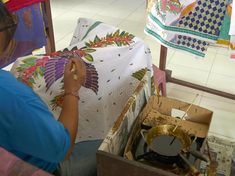 GIANYAR, INDONESIA - JUNE, 19, 2017: wide view of an artist painting batik cloth on the island of bali. GIANYAR, INDONESIA - JUNE, 19, 2017: wide view of an royalty free stock photography