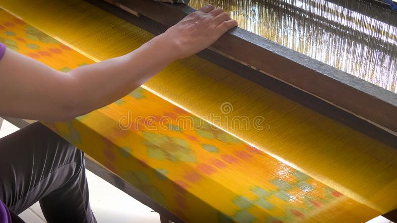 GIANYAR, INDONESIA - JUNE, 19, 2017: a worker weaving batik cloth at a factory in bali. GIANYAR, INDONESIA - JUNE, 19, 2017: a worker weaves colorful batik cloth stock image