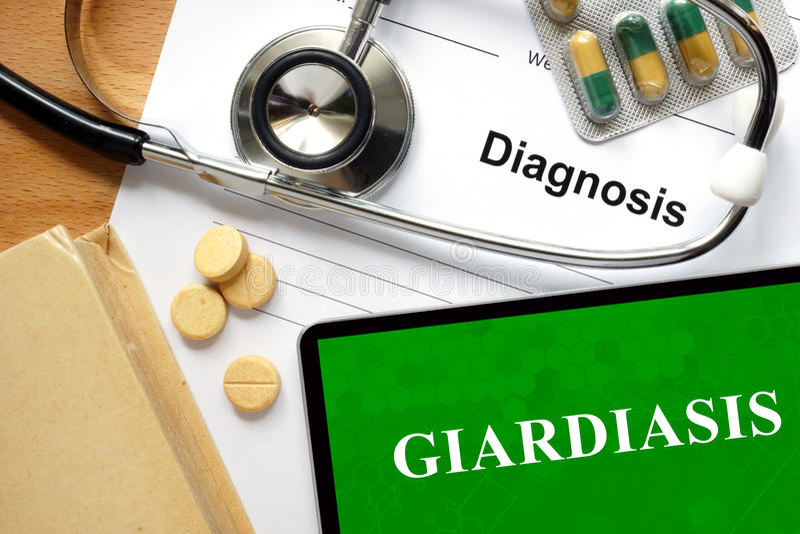 Giardiasis da palavra em um papel e em comprimidos fotografia de stock