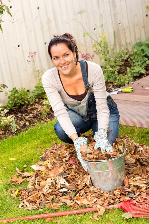 Giardinaggio di riempimento di caduta delle foglie del secchio della donna felice immagini stock