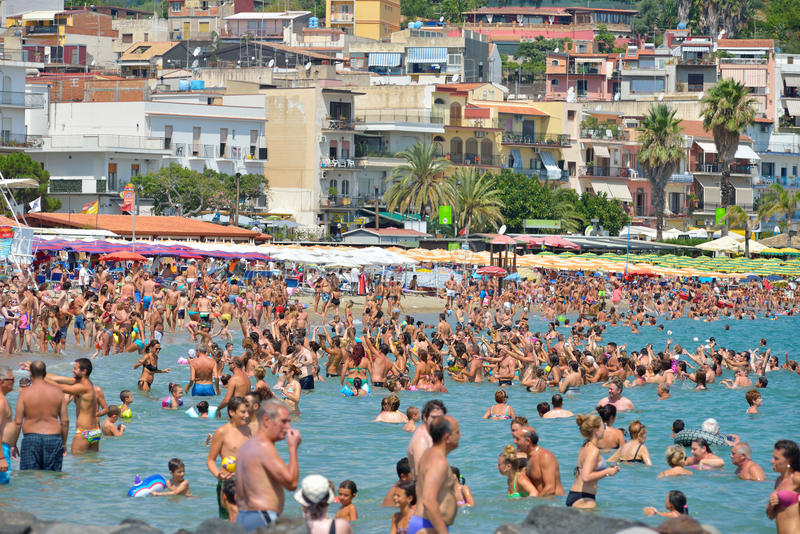 GIARDINI NAXOS, ITALIË - AUGUSTUS 2015: Groep toeristen bij het strand van Giardini Naxos, Sicilië, Italië in Augustus, 2015, Ita stock foto