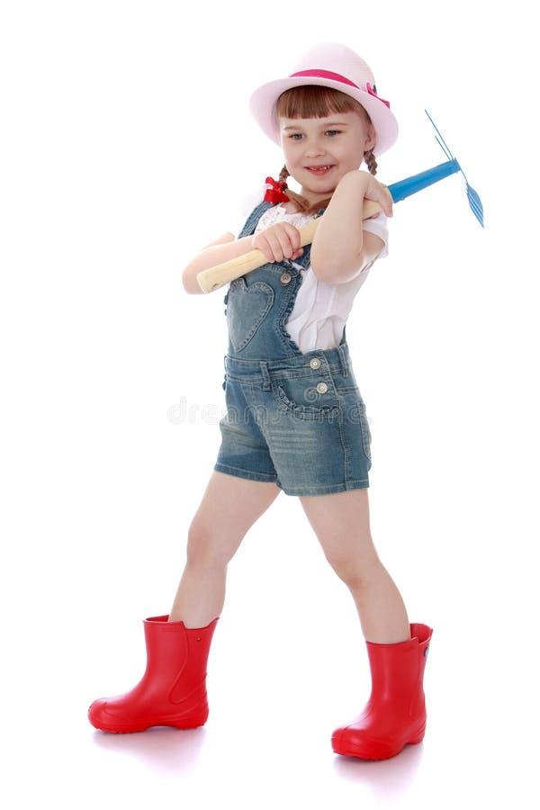 Giardiniere allegro della ragazza in stivali di gomma fotografie stock