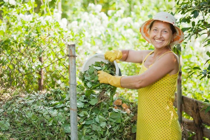 Giardiniere che concima con la composta erba fotografia stock