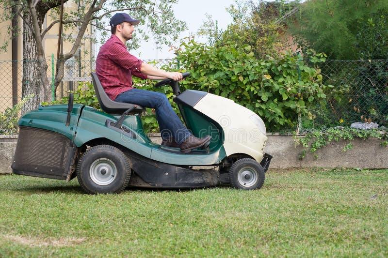 Giardiniere che taglia l'erba di un gardenon una falciatrice da giardino fotografia stock