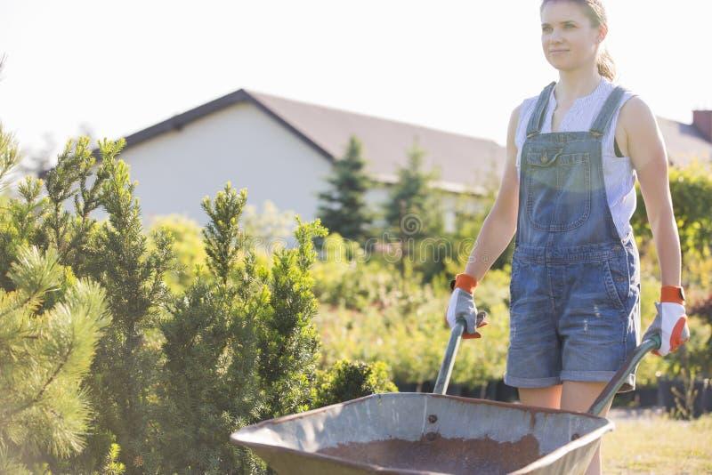 Giardiniere femminile che spinge carriola alla scuola materna della pianta fotografia stock libera da diritti