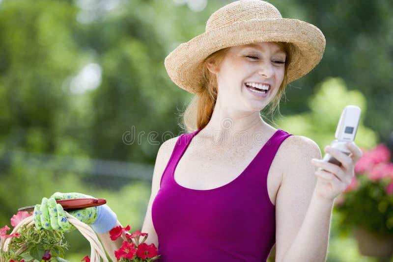 Giardiniere grazioso con il telefono delle cellule fotografie stock libere da diritti