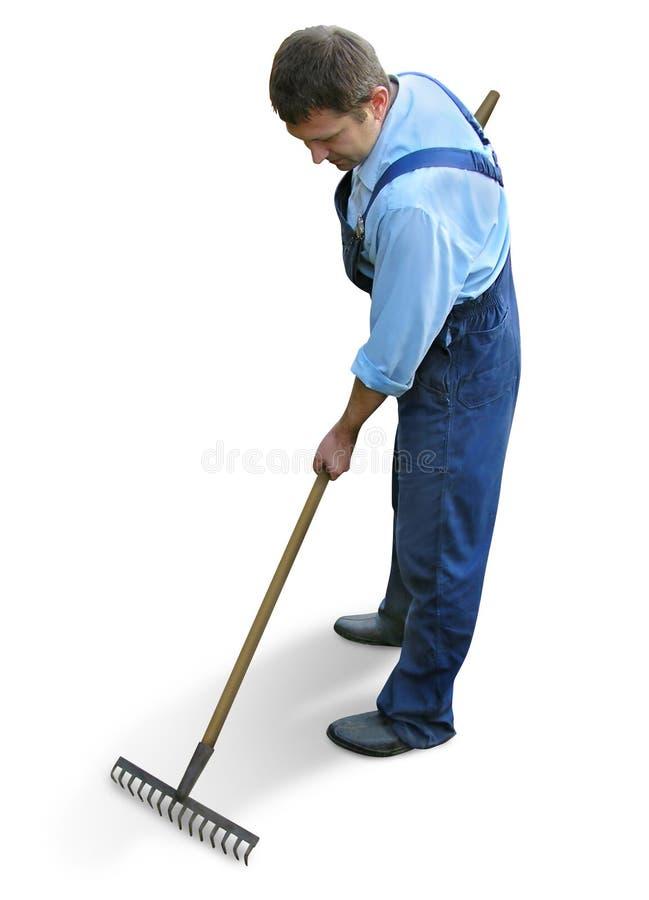 Giardiniere - operaio in vestiti da lavoro, rastrellanti il giardino immagini stock libere da diritti