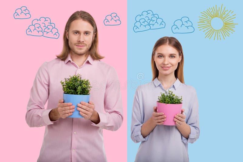 Giardinieri allegri che sorridono mentre stando con i vasi da fiori fotografia stock