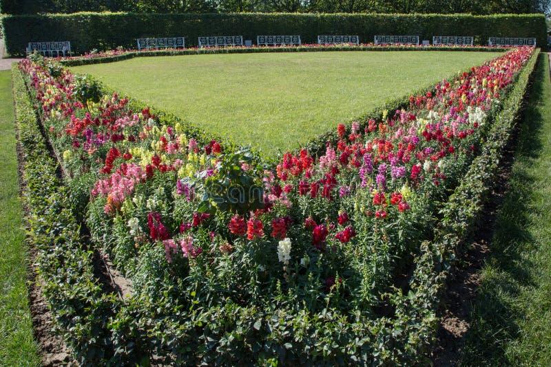 Giardino convenzionale con il giardino bianco del banco fotografie stock