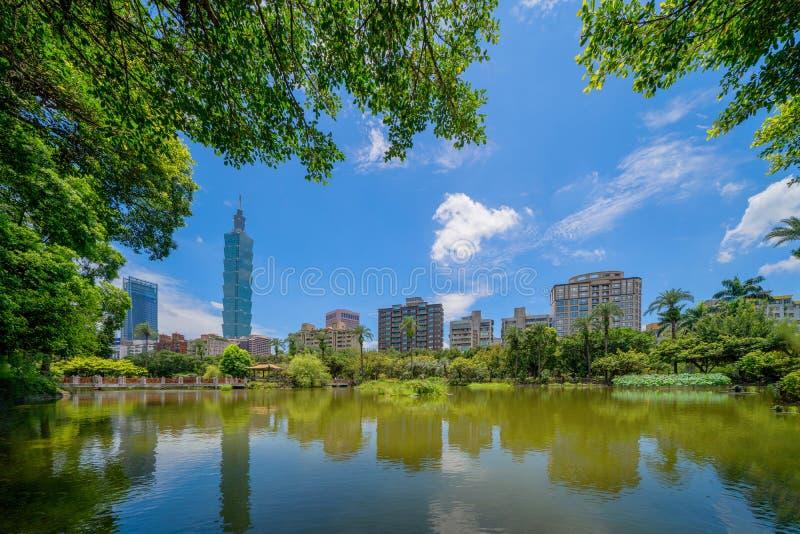 Giardino del parco di Taipei e riflessione delle costruzioni dei grattacieli Distretto e centri di affari finanziari in città urb immagine stock libera da diritti