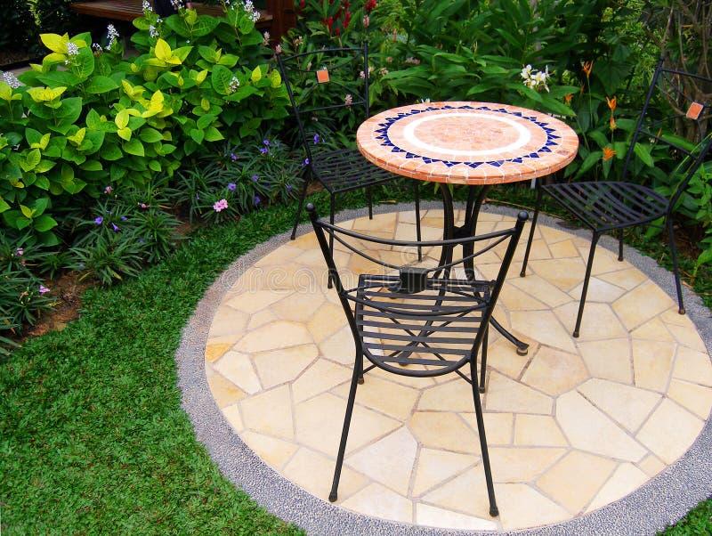 Giardino grazioso con la pavimentazione e le mobilie fotografie stock libere da diritti