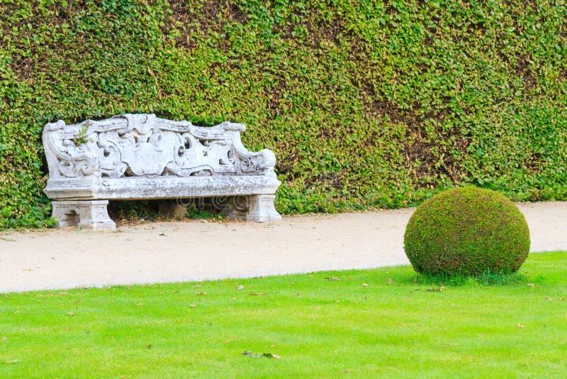 Giardino inglese ornamentale con il banco di pietra fotografia stock libera da diritti