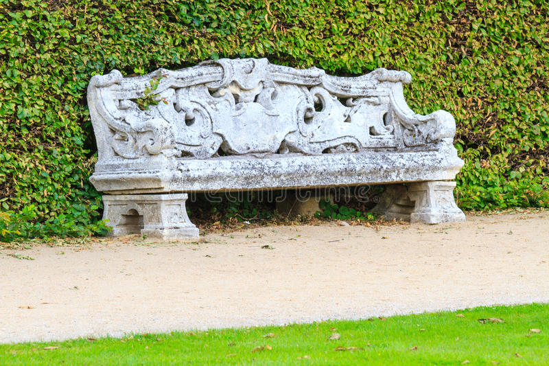 Giardino inglese ornamentale con il banco di pietra fotografie stock libere da diritti
