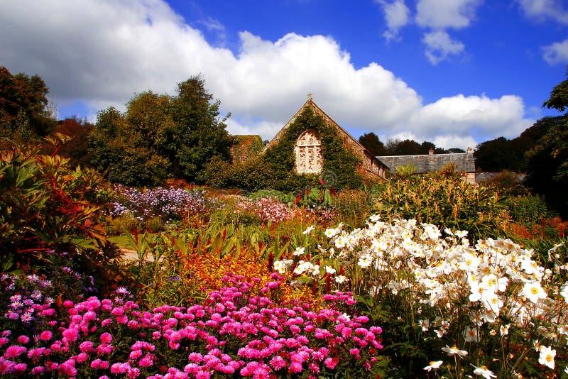 giardino magico stupefacente con i fiori e la casa immagine stock