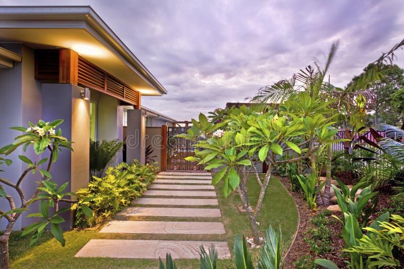 Giardino moderno della casa con illuminazione variopinta sotto il cielo immagine stock