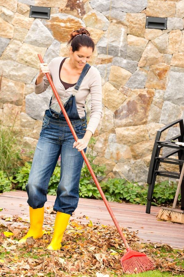 Giardino sorridente di lavoro domestico di caduta delle foglie di rastrellamento della donna fotografia stock