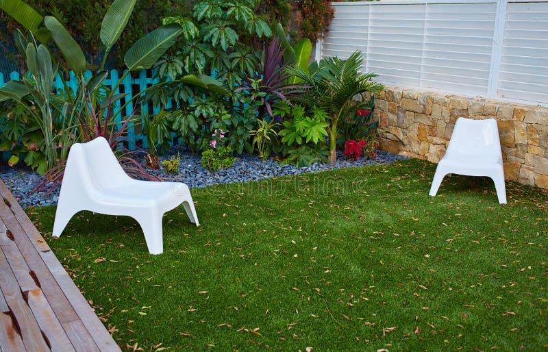 Giardino tropicale con la piattaforma artificiale di legno del tappeto erboso dell'erba immagine stock libera da diritti