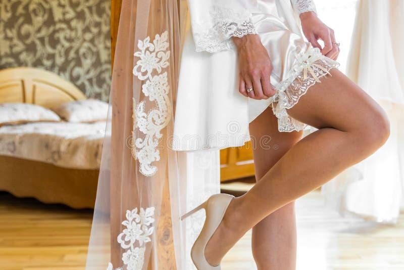Giarrettiera d'uso di nozze della sposa Una donna dimostra le sue gambe sexy immagini stock